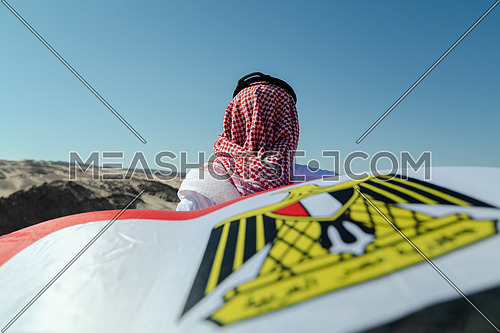 Bedouin man from his back holding Egyptian Flag in Sinai Trail in Ain Hodouda by day.