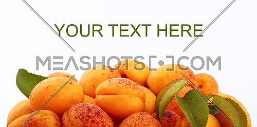 Heap of fresh ripe mellow apricots with green leaves over white background, close up, side view