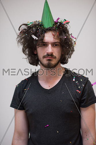 young man celebrating new year and chrismas party while blowing confetti decorations to camera