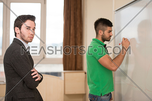 Young Arabic Student Writes Some Answer on The Whiteboard And The Teacher Observes Him