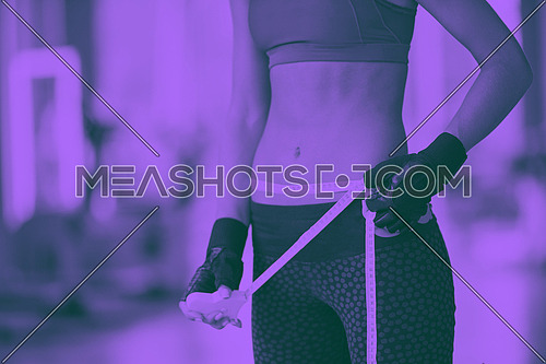 young fit woman measuring belly on a training  in  fitness gym duo tone