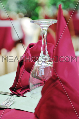 Restaurant table with empty wine glass and red table decoration