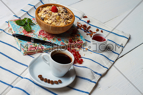 A breakfast setting with  a cup of coffee and a bowl of oat and yogurt