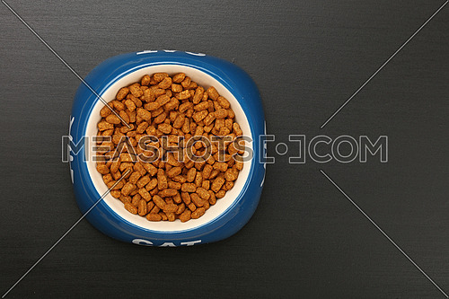 Brown dry cat food portio in blue and white ceramic bowl with cat word on black floor, close up, top view, personal perspective