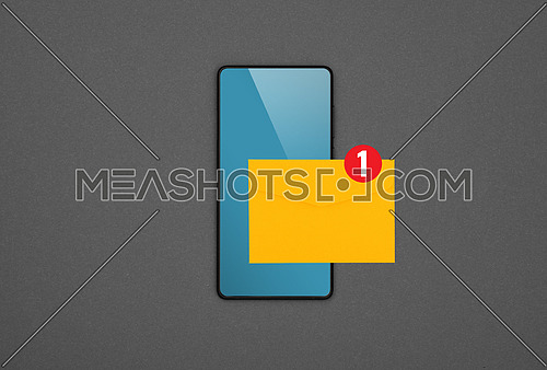 Close up one black smartphone with blank blue screen and yellow envelope of new message over grey paper background, flat lay, directly above