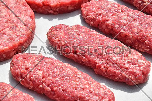 Raw red meat burgers, kebabs or patty cutlets of minced ground beef, lamb, pork on white parchment paper ready for cooking