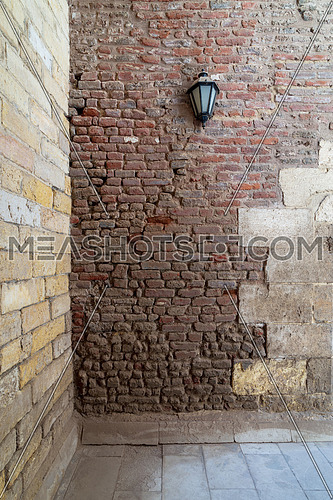 Front view of grunge weathered two perpendicular uneven stone bricks wall with one lantern, Medieval Cairo, Egypt
