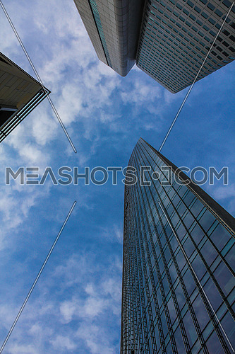 tall buildings reflecting blue sky and some clouds
