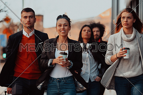 Happy business people walking in the street after a successful day of work and discussing the closed deals. High-quality photo