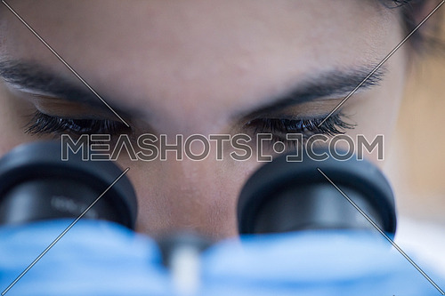 portrait of a young middle eastern woman with a microscope in a large modern laboratories