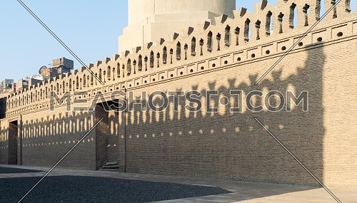 Stone bricks old decorated fence with wooden door and shadows of decorations of the opposite fence, Mosque of Ibn Tulun, Old Cairo, Egypt