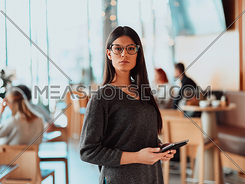 Portrait of happy smiling beautiful business woman holding tablet