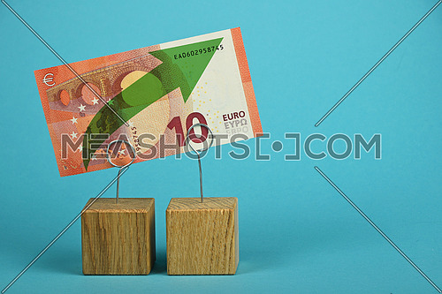 Growth and support of European economy and Euro currency, ten Euro banknote with green arrow up on two holders over blue background