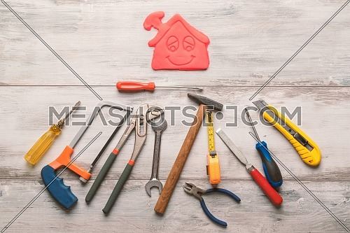 Set of work tool on rustic wooden background with icon of house in space, industry engineer tool concept.still-life.