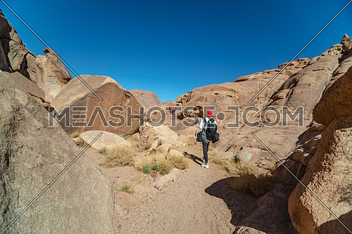Long shot for a male tourist exploring Sinai Mountain at day.