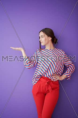 Portrait of happy smiling young beautiful woman in a presenting gesture with open palm isolated on purple background. Female model in modern fashionable clothes posing in the studio