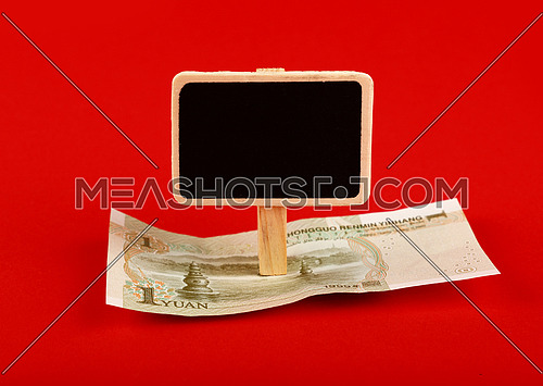 Close up one Chinese Yuan paper currency banknote and blank chalk blackboard sign with copy space over red background, high angle view