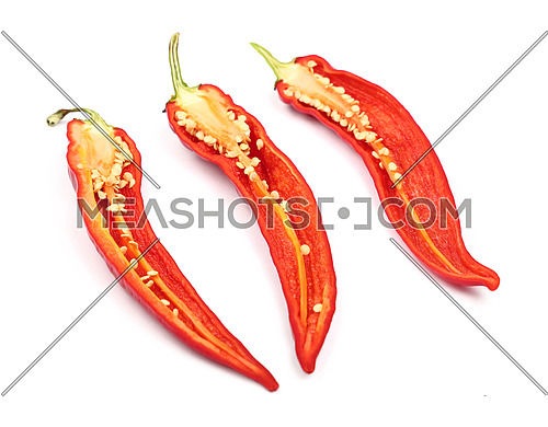 Three cut halves of fresh red hot chili peppers isolated on white background, close up, high angle view