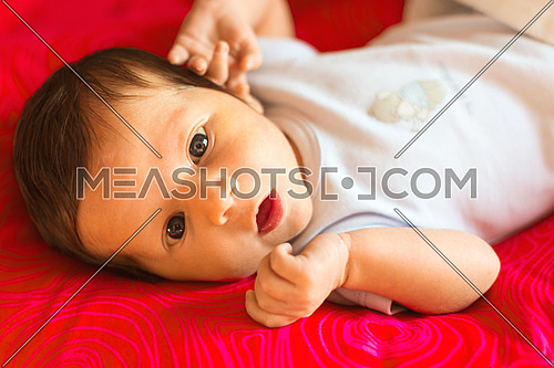 Newborn boy looks surprised with his mouth open on a red background.