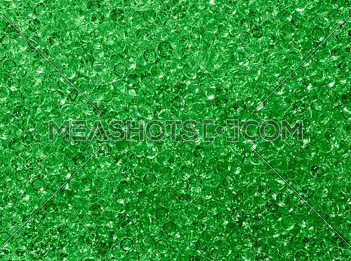 Close up background pattern of many green rhinestone crystals, elevated top view, directly above
