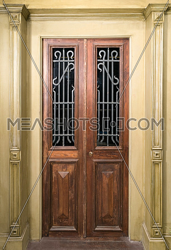 Vintage wooden brown door with glass and metal  ornate grid