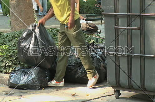 Medium shot for a male Park worker disposes of garbage in New York city at day.