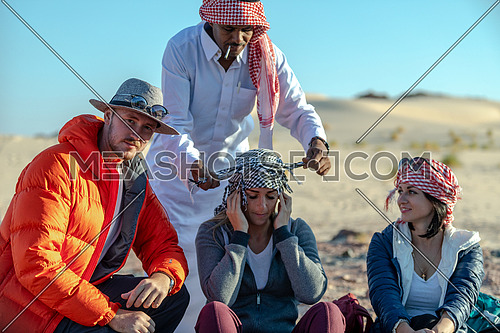 mid shot for a bedouin male helping female tourist to wear traditional bedouin headscarf at Ain Hodouda in Sinai at day.