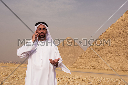 young middle eastern businessman  speeking by phone with egyptian giza pyramids in background