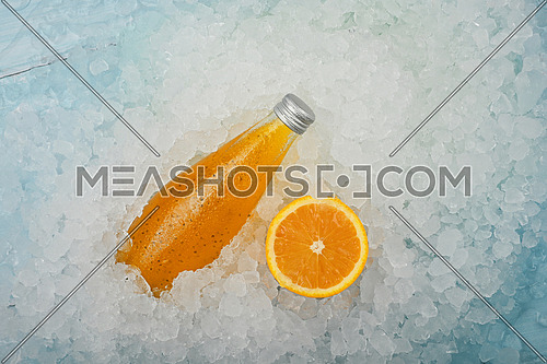 Close up one glass bottle of cold orange juice cocktail drink with chia seeds and half cut orange on crushed ice at retail display, elevated high angle view, directly above