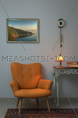 Vintage Furniture - Interior composition of retro orange armchair, vintage wooden beige table, illuminated antique table lamp, old books, and pendulum clock over off white wall and orange carpet