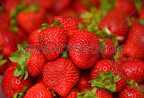 Close up heap of fresh red strawberry berries on retail display of farmers market, high angle view