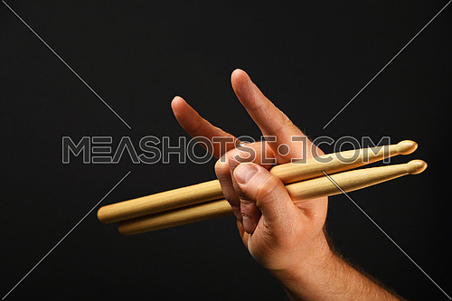 Man hand holding two drumsticks with devil horns rock metal gesture sign over black background, side view