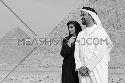 a black and white portrait of Emiratie man and his wife as tourists at the pyramids