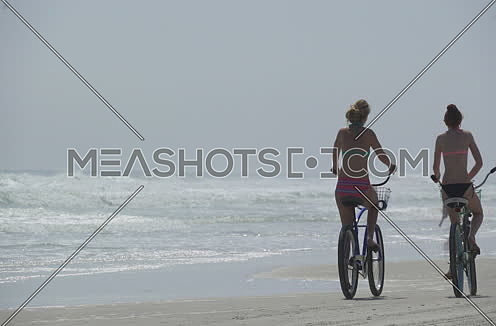 two women cycling by the beach