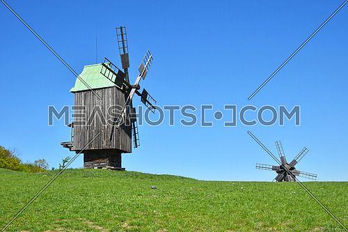 Rural meadow landscape with two old wooden windmills, one behind horizon line, and clear blue sky