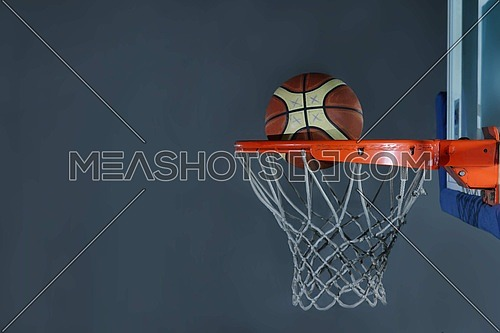 Basketball ball,  board and net  on grey  background in gym indoor