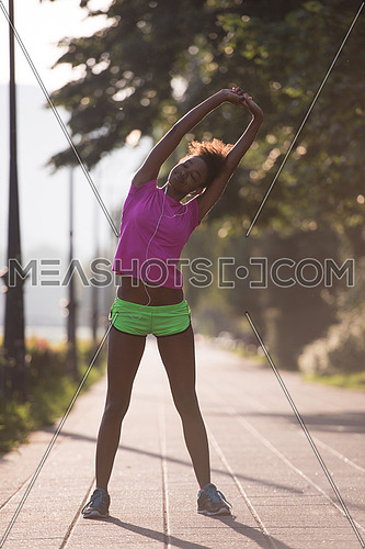 young beautiful African American woman doing warming up and stretching before the morning run with the sunrise in the background