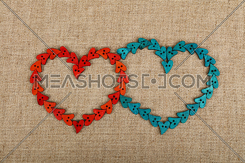 Two hearts together shaped of red and blue handmade wooden sewing buttons on linen canvas, elevated top view