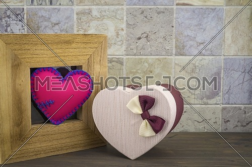 Handcrafted pink heart in a wooden frame with a heart shaped gift box against a tiled background