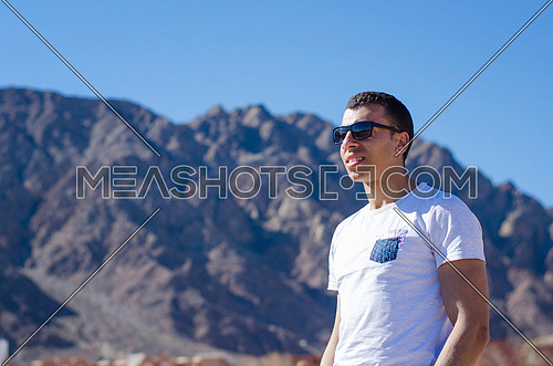 an arab looking man wearing sunglasses with mountains in the background