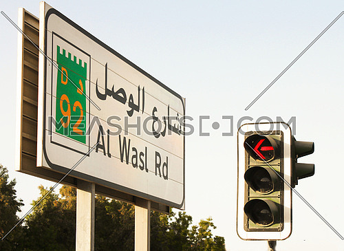 Al Wasl street sign in Dubai with a red traffic signal
