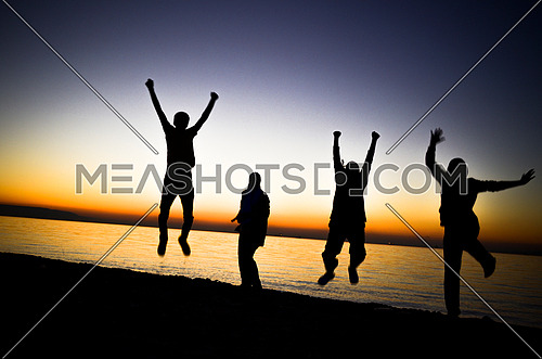 4 friends having fun and jumping at the beach by sunset magic hour
