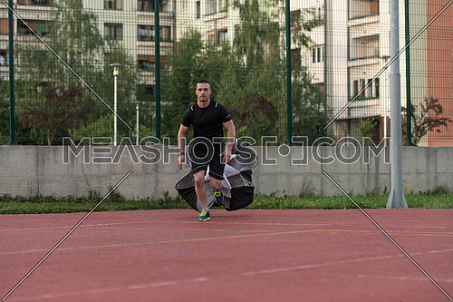 Young Man Running With Parachute On Sports Field