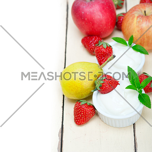 fresh fruits and whole milk yogurt on a rustic wood table