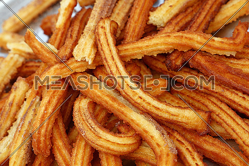 Close up tray of sweet fresh churros, traditional Spanish or Portuguese deep fried dough pastry snack cooked, high angle view