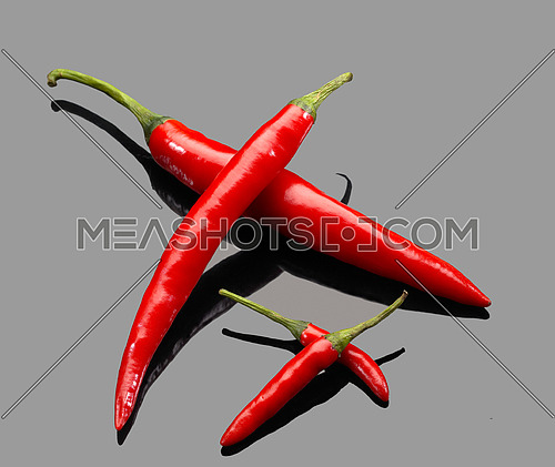 fresh red chili peppers over grey reflective surface