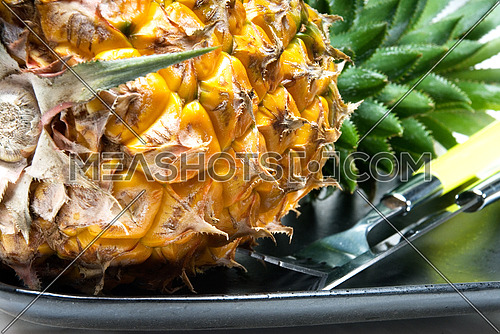ripe vivid pineapple on a black plate with knife and fork