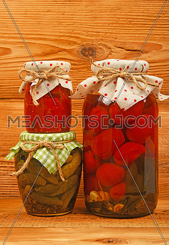 Three glass jars of homemade conserves, eggplant pepper salad, pickled tomatoes and cucumbers with textile decoration over brown unpainted wood