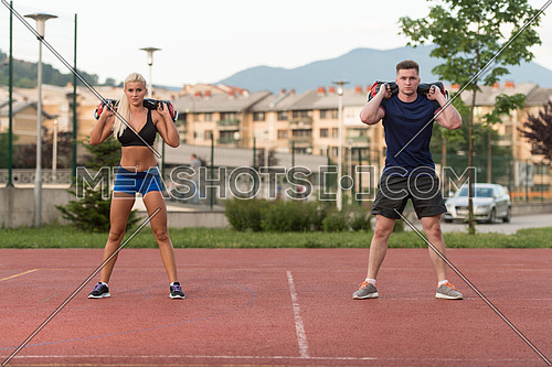 A Group Of Young People In Aerobics Class Performing Bag Squat Exercise Outdoor