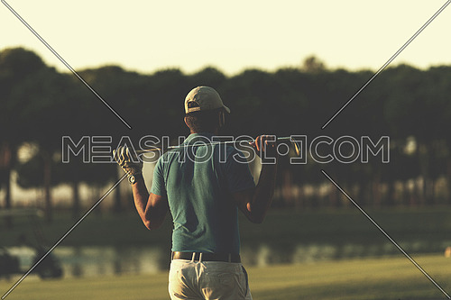 golfer  from back looking to ball and  hole in distance, handsome middle eastern golf player portrait from back with beautiful sunset in background